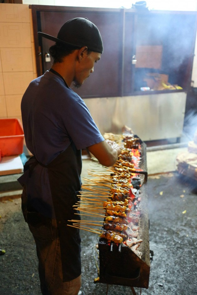 A worker preparing satay on the grill.