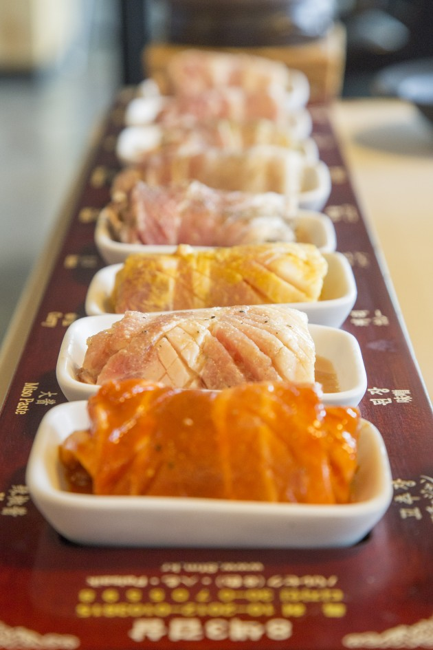 The eight coloured meat rolls are arranged according to taste strength.