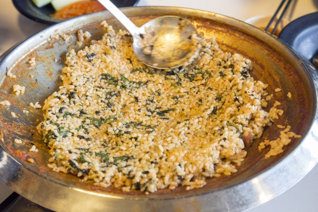 The rice soaks up the remaining soup as it is being fried.