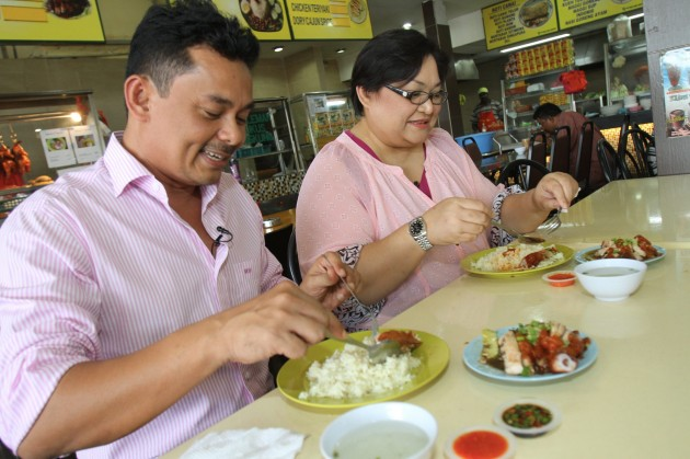 Suria FM DJs Halim Othman (left) and Adibah Noor enjoying their chicken rice at Barry's stall in Restoran Jamal Mohamed, Kelana Jaya.