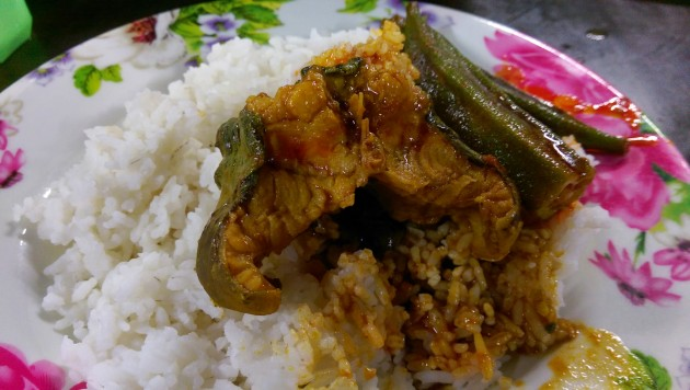 A piece of curried caffish over a plate of hot rice.
