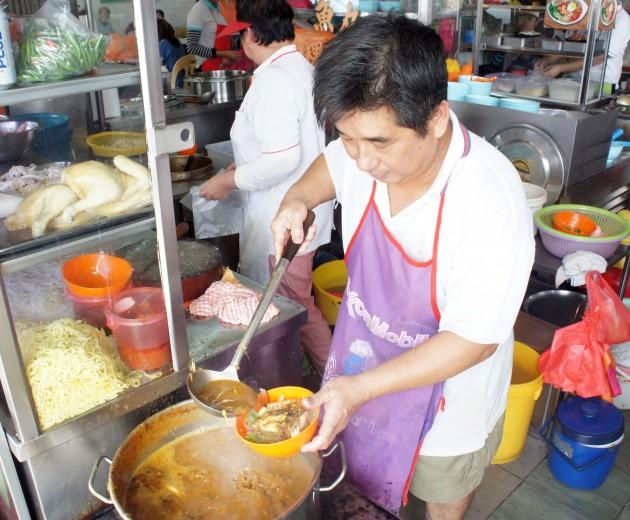 Penang Laksa stall owner Ooi preparing orders for customers.