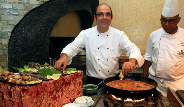 Chef Jordi Gimeno (left) preparing Black Rice, Sea and Mountain Paella to be served fresh to diners.