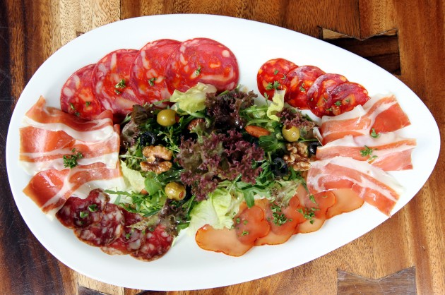 The NBDD Platter, a combination of  Serrano ham, lomo (cured pork tenderloin)  and a selection of chorizo slices with  garden greens with balsamic vinegar,  walnut, almonds and olives.