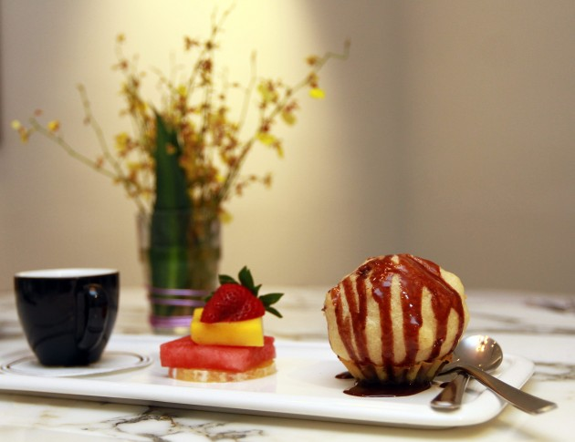 The trio of desserts comprises flat white coffee, fruit slices and fried ice cream.