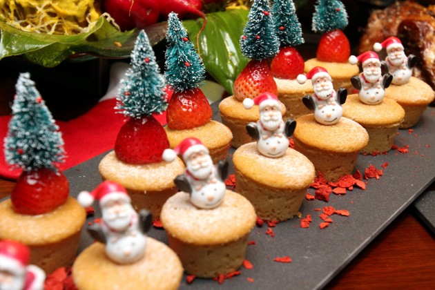 A colourful assortment of cupcakes decorated with mini Santa Claus and pine trees.