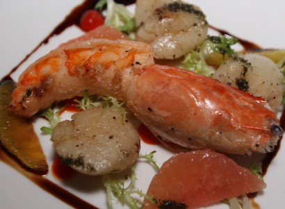 Tasty seafood The warm seared scallops and prawn with Ruby Red Grapefruit, Piquillo Coulis, orange and Frisee Salad served with balsamic reduction.