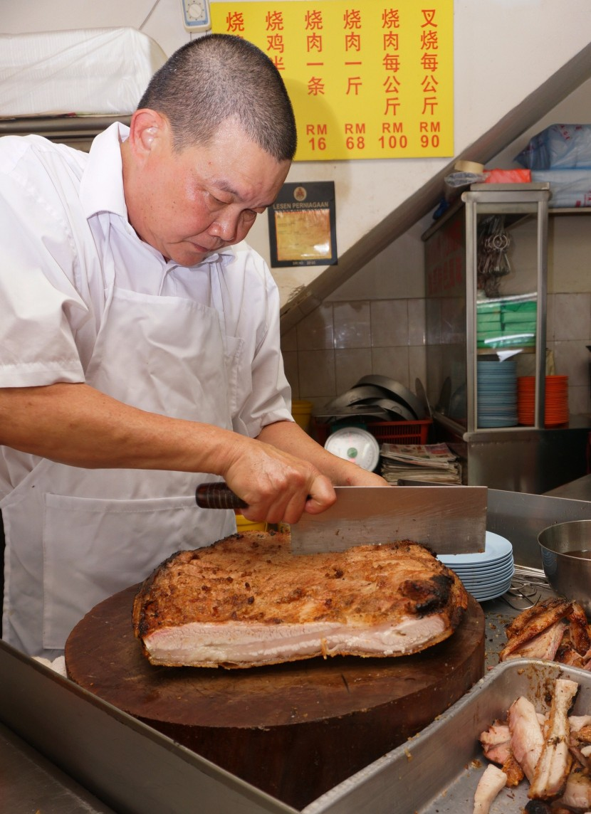 Hard at work: Wong begins serving his famous roast pork at 12.30pm and does not stop chopping up meat until 3pm.