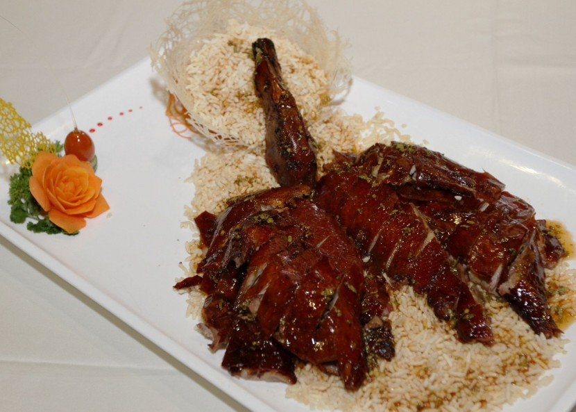 Roasted duck served with plum sauce and crispy rice.