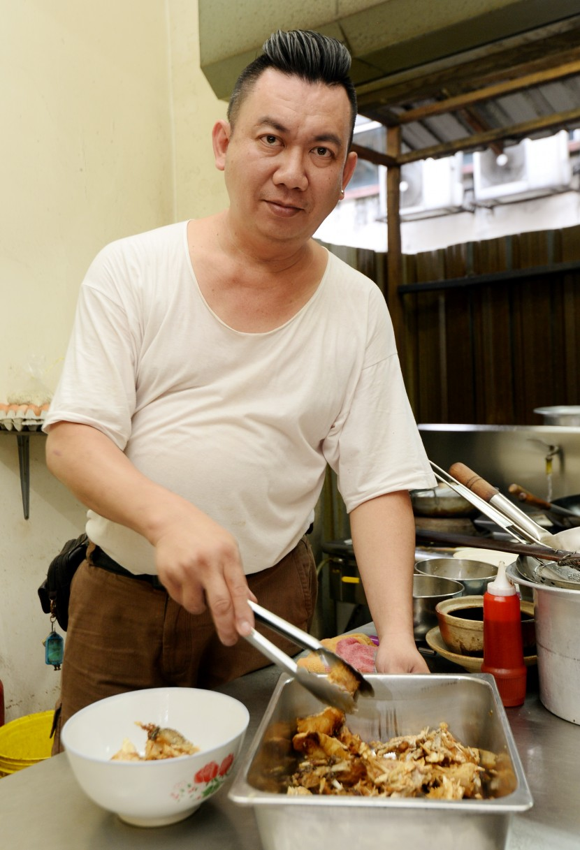 Satisfying meal: Leong preparing the fried fish head before putting it in the soup.
