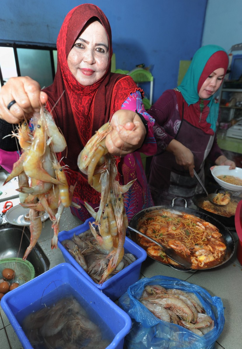 Mee Udang Kak Ju's Julia Ahmad showing off the big prawns her village's fishermen supply to her while her assistant Yani Manan, ladles steaming bowls of prawn noodles for waiting customers.