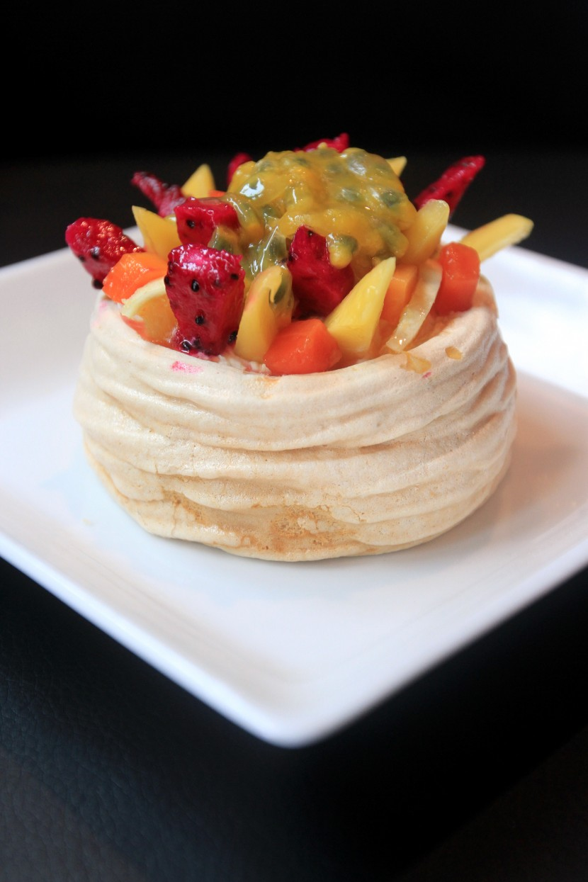 The pavlova is topped with a selection of fruits.