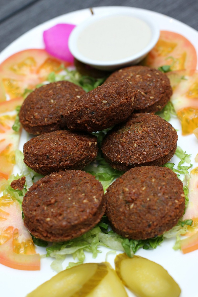 The falafel is fried beans and chickpea paste shaped into a ball, that is served with tahini sauce.