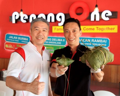 Third generation bak chang master Lor Kah Fai from Cintra Food Corner (right) and Penang One general manager Gary Teoh showing the giant bak chang and the normal sized one.