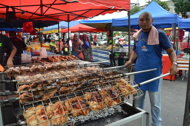 Faqrul Ismadi Oman turning the chickens over a charcoal fire at the Ramadan Bazaar.