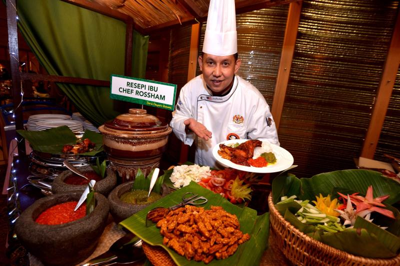 Sunway Putra hotel Coffeehouse executive chef Rossham Rosli posing with a plate of Nasi Ayam Goreng Kampung at his stall.