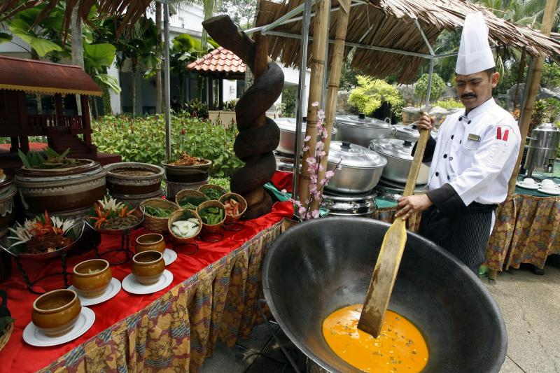 The Royale Bintang Resort & Spa Seremban Malay sous chef Ahmad Mahamod stirring gulai kawah, a curry cooked in a large kawah (wok).