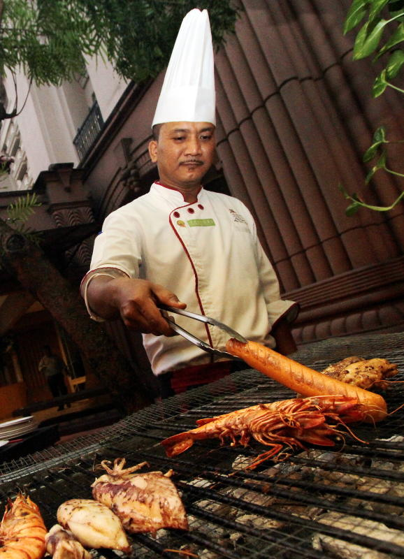 A chef grilling a sausage so that diners can enjoy their dish on the spot.