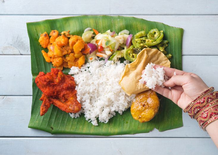 31734001 - indian woman eating banana leaf rice, overhead view on wooden dining table.
