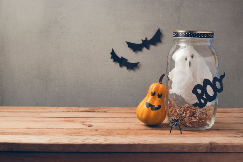 64134289 - halloween holiday decoration with ghost in jar and pumpkin with scary face on wooden table