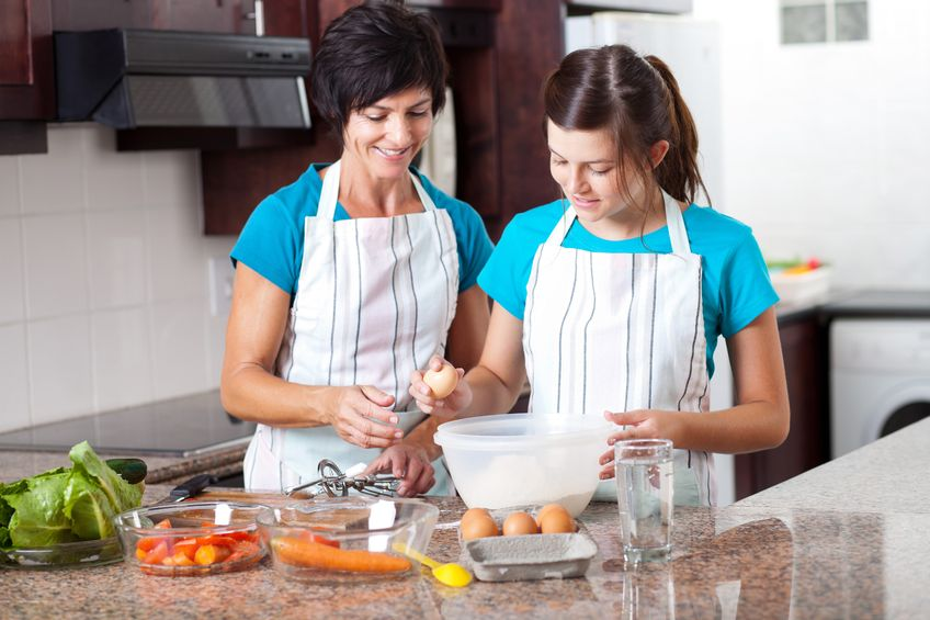 Mother teaching child to cook during school holidays