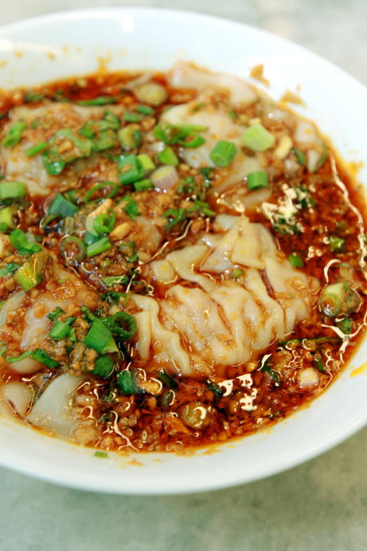 The Sichuan-Style Dumpling is served in a gravy of vinegar and chilli oil, topped with garlic, coriander and spring onion.