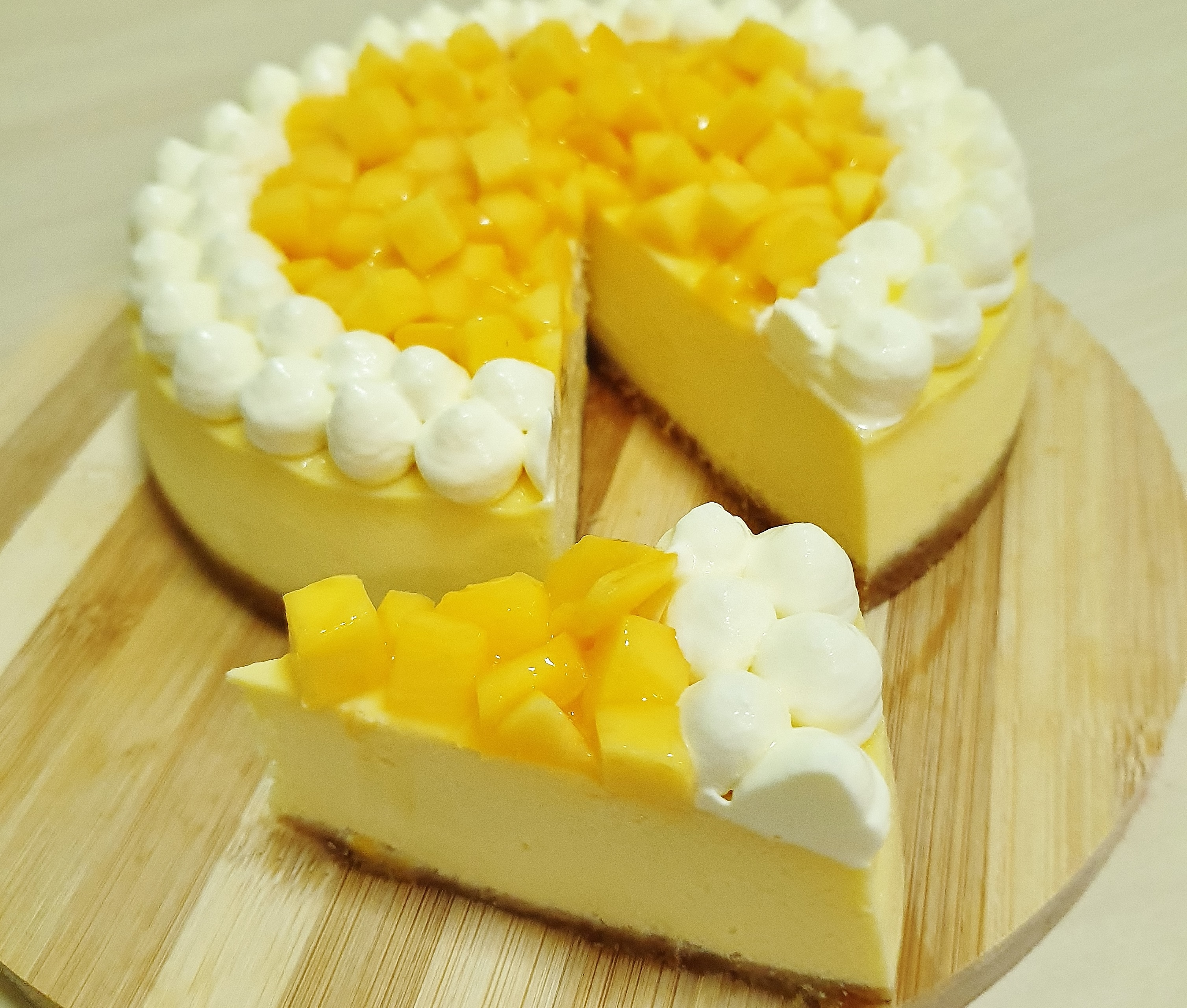 Mango Cheesecake with Whipped Cream and Fresh Mango