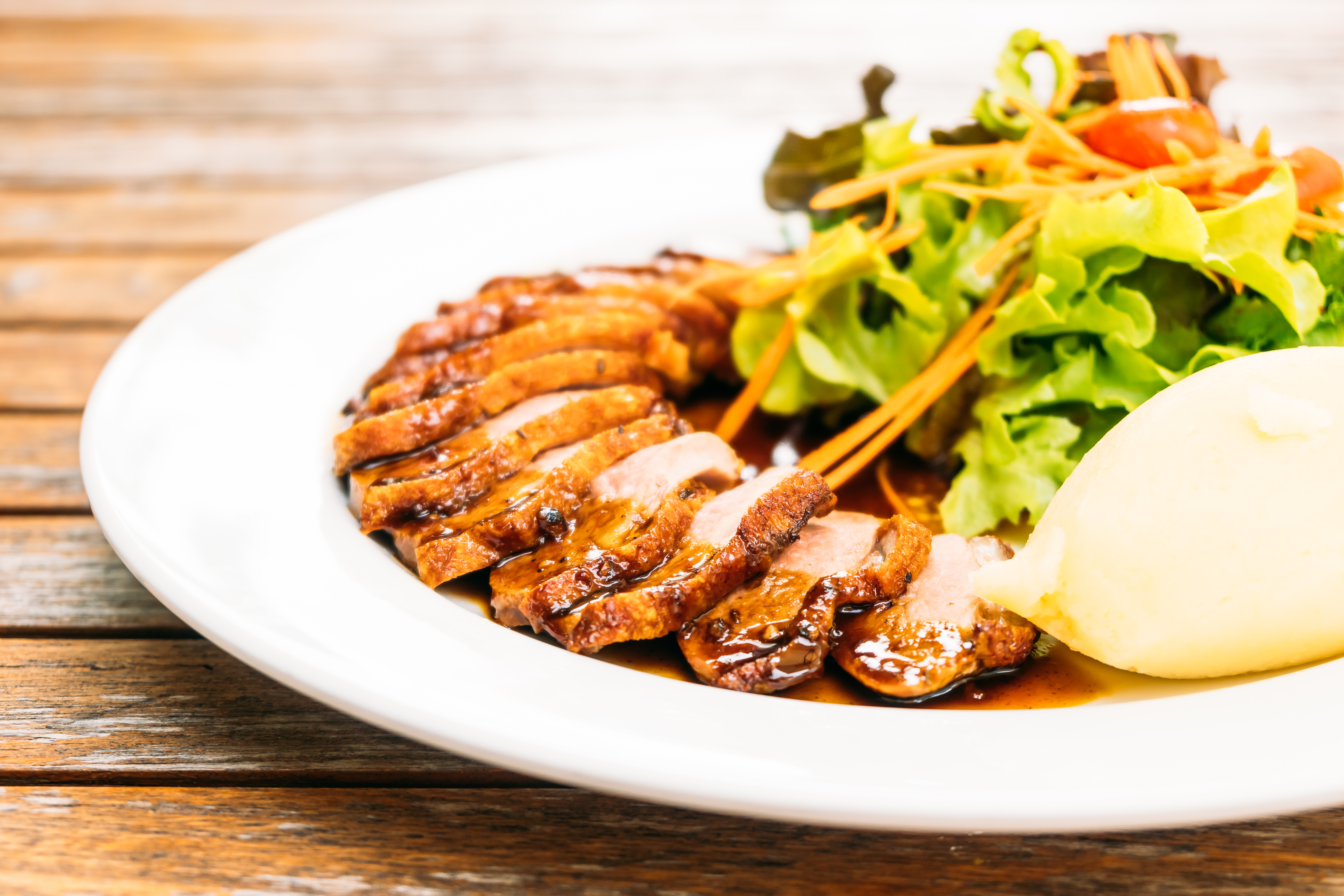 Grilled duck meat breast with vegetable in white plate